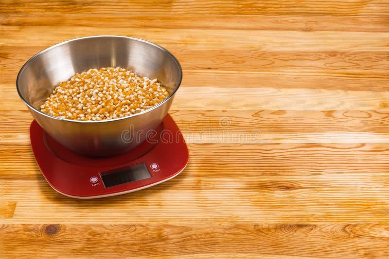 Kukurudza w pucharze na elektronicznej skali na naturalnym drewnianym tle z kopii przestrzenią zdjęcia royalty free
