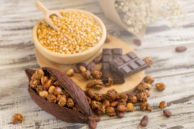 Kukurydzani nasiona w drewnianych talerzach i popkornie z karmelem i choco zdjęcia royalty free