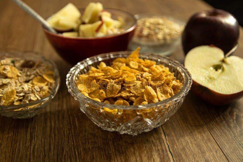 Kukurydzani płatki w krystalicznym pucharze, świeżym czerwonym organicznie jabłku i innym zdrowym jedzeniu, zdjęcia royalty free
