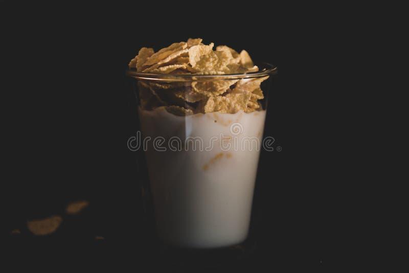 Kukurydzani płatki z mlekiem w szklanej filiżance odizolowywającej na czerni zdjęcie stock