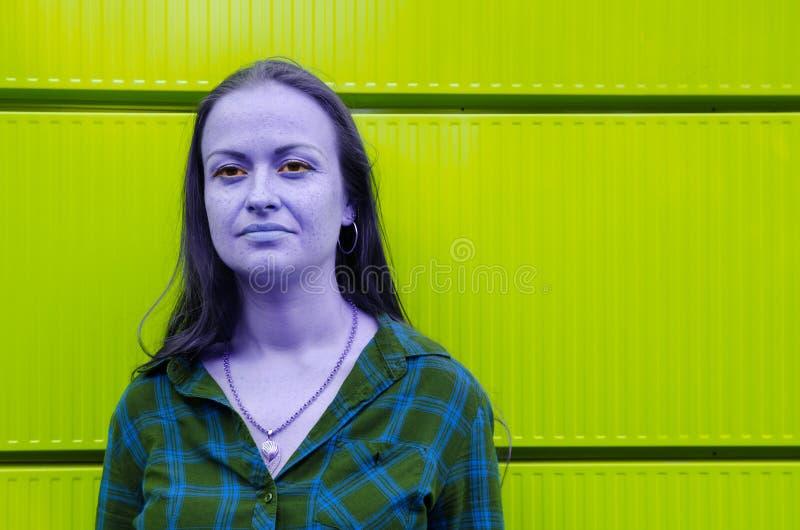 Kulör blå flicka mot den gröna syrliga färgväggen Psykedelisk stil arkivfoto