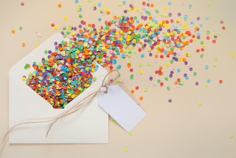 Kulör konfetti häller ut ur kuvertet Små cirklar av sänkan royaltyfri foto