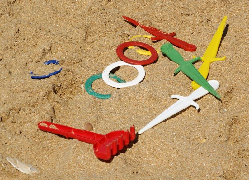 Kul?r plast- leksaker p? en sandig strand arkivbilder
