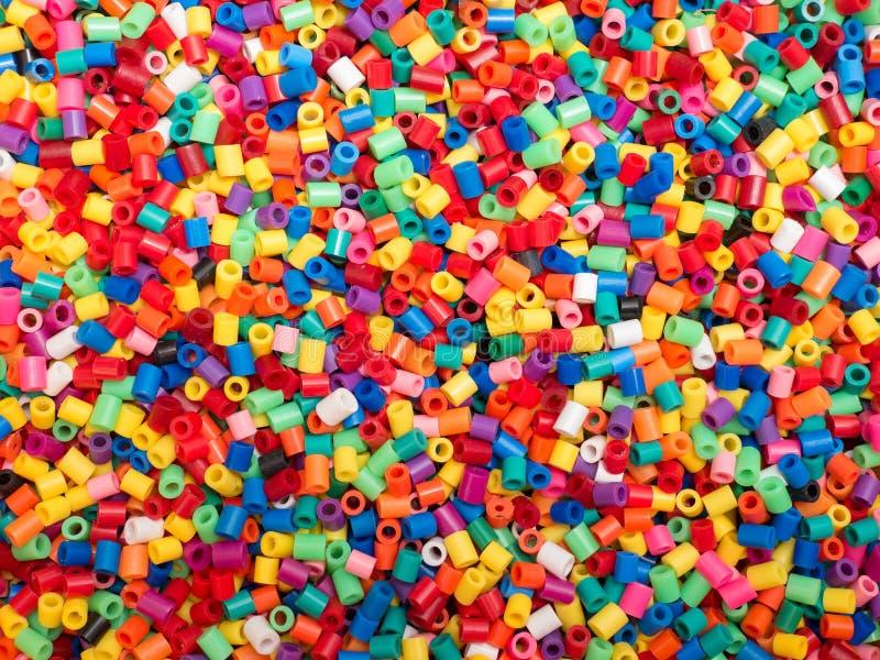 Kulör plast- pryder med pärlor bakgrund arkivbild