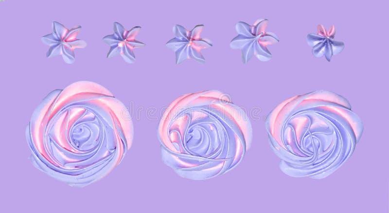 kulör rosa färg-violett marshmallow i formen av en blomma för garnering av en festlig efterrätt på en isolerad purpurfärgad paste arkivfoto