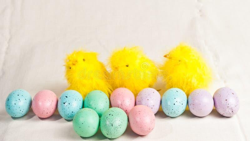 Kulöra ägg för påsk och tre fågelungar arkivbilder