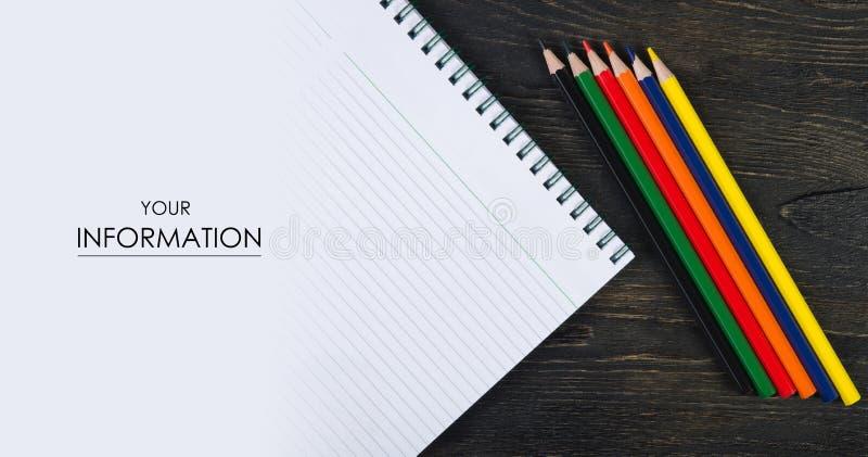 Kulöra blyertspennafärgpennor och anteckningsbokfoto över arkivbild