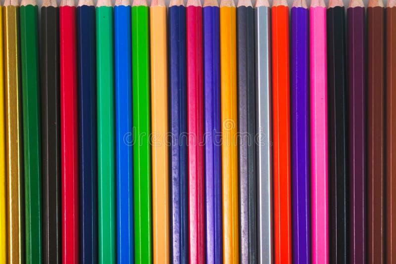 Kulöra blyertspennor förläggas i rader royaltyfria foton
