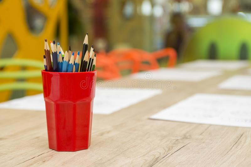 Kulöra blyertspennor i ett exponeringsglas på en tabell royaltyfri fotografi