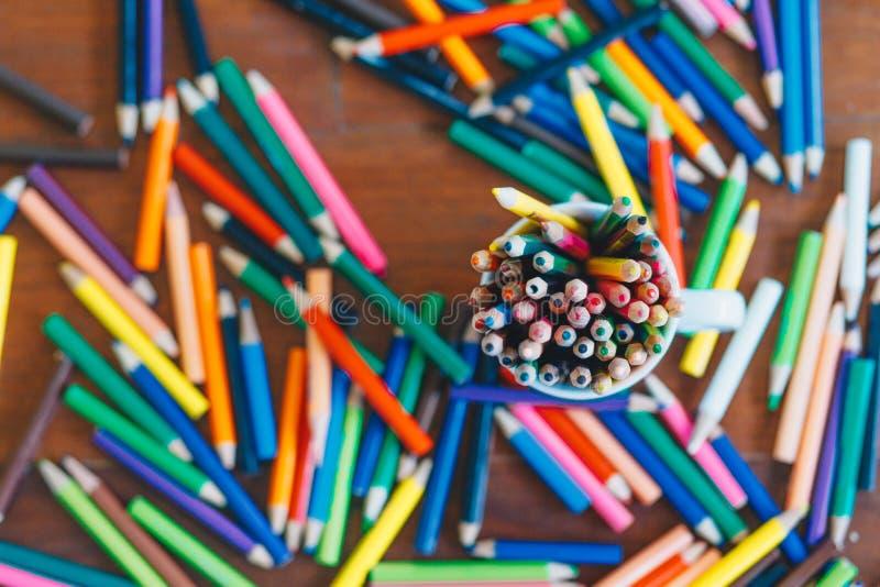 Kulöra blyertspennor i ett exponeringsglas på träbakgrund arkivbilder