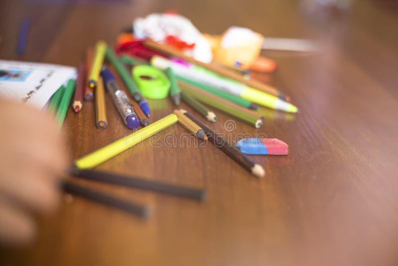 Kulöra blyertspennor i röra på tabellen royaltyfri bild