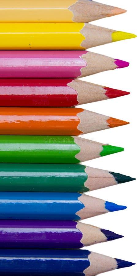 Kulöra blyertspennor i rad, isolerat på en vit bakgrund arkivbilder