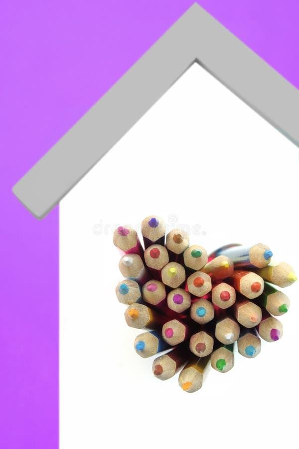Kulöra blyertspennor klibbar ut från det hjärta formade fönstret arkivfoton