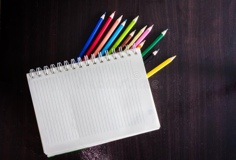 Kulöra blyertspennor och anteckningsbok på wood textur arkivbild