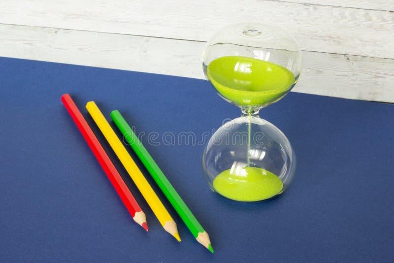 Kulöra blyertspennor och ett timglas på en träbakgrund arkivbilder