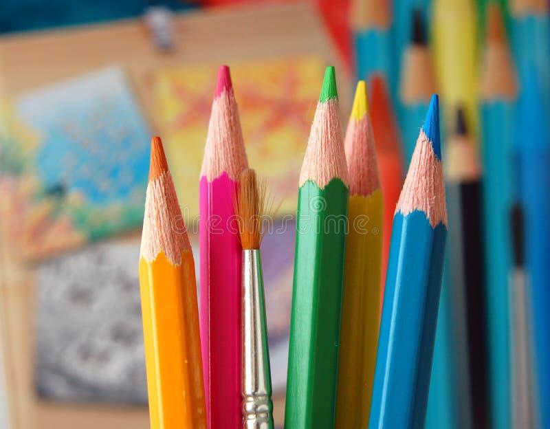 Kulöra blyertspennor och målarfärgborste royaltyfria bilder