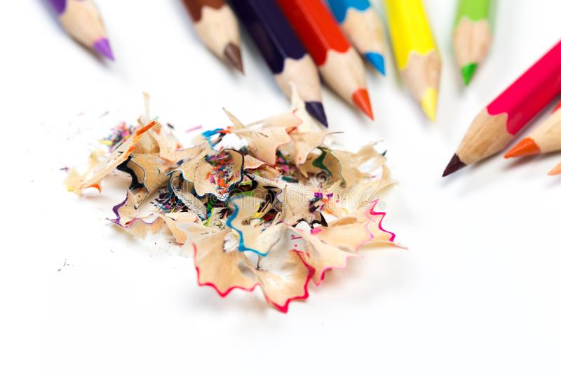 Kulöra blyertspennor och shavings med blyertspennor Vässare av blyertspennor på en vit bakgrund arkivfoto