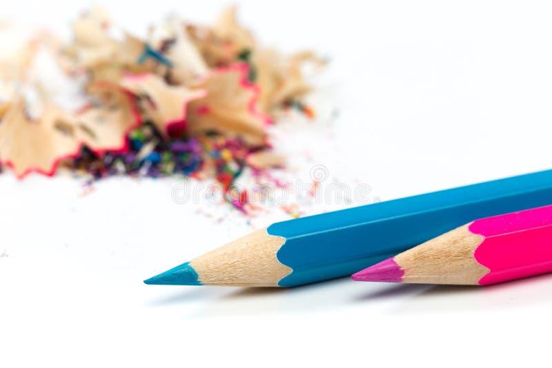 Kulöra blyertspennor och shavings med blyertspennor Vässare av blyertspennor på en vit bakgrund royaltyfri fotografi
