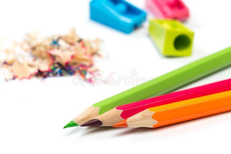 Kulöra blyertspennor och shavings med blyertspennor Vässare av blyertspennor på en vit bakgrund royaltyfri bild