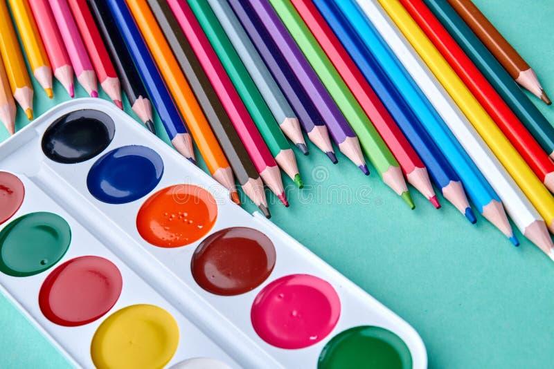 Kulöra blyertspennor och vattenfärgpalettbakgrund arkivbilder