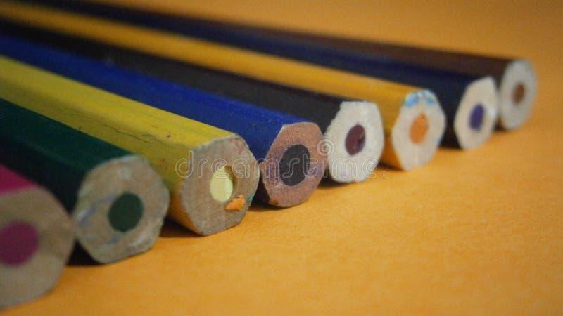 Kulöra blyertspennor på en gul bakgrund royaltyfria foton