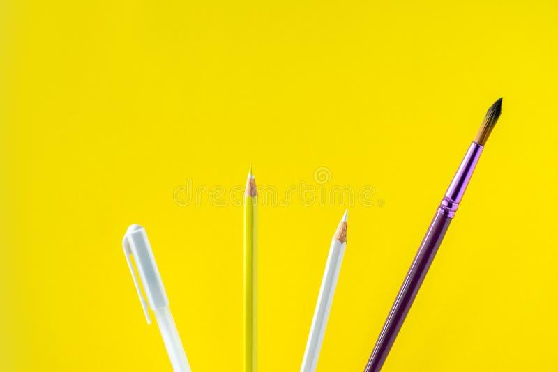 Kulöra blyertspennor på en gul bakgrund med utrymme för text arkivfoto