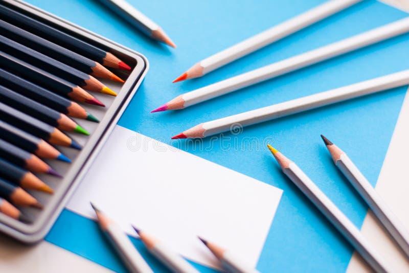 Kulöra blyertspennor på en ljus blå bakgrund och en tom affär royaltyfri bild