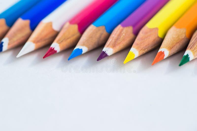 Kulöra blyertspennor på en pastellfärgad bakgrund till en punkt med utrymme för text fotografering för bildbyråer