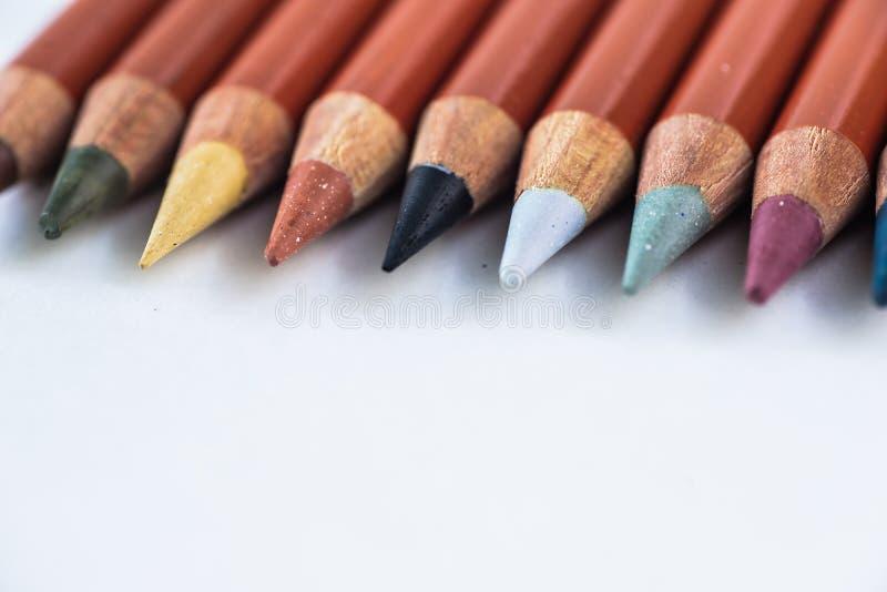 Kulöra blyertspennor på en pastellfärgad bakgrund till en punkt med utrymme för text royaltyfria bilder