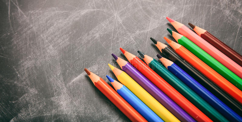 Kulöra blyertspennor på ett svart bräde royaltyfria bilder