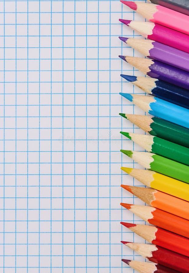 Kulöra blyertspennor på notepaden royaltyfria foton