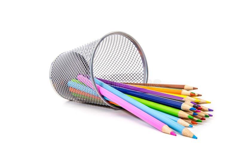 Kulöra blyertspennor på utspilld vit som spills/ royaltyfri fotografi