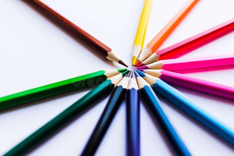 Kulöra blyertspennor på vit bakgrund, i en cirkel royaltyfria bilder