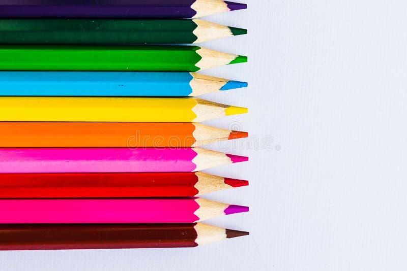 Kulöra blyertspennor på vit bakgrund som lämnas royaltyfri foto