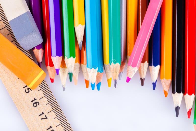 Kulöra blyertspennor, radergummi och linjal arkivbild