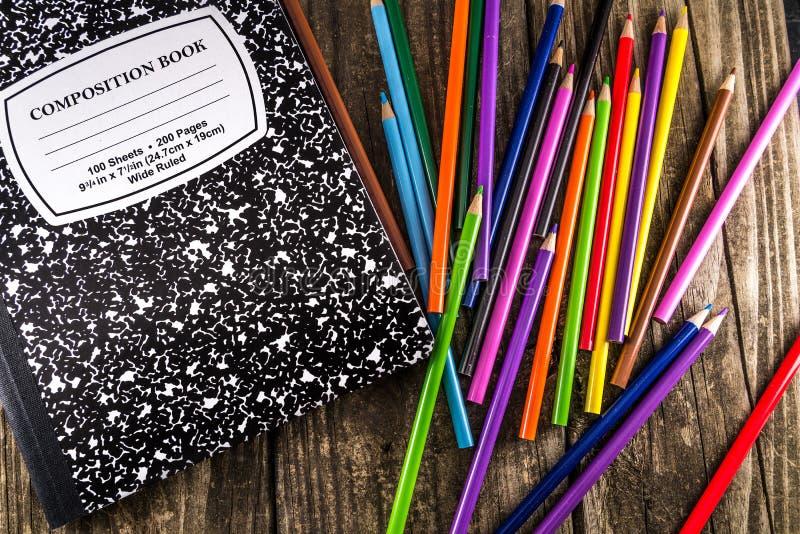 Kulöra blyertspennor & sammansättningsanteckningsbok royaltyfria bilder