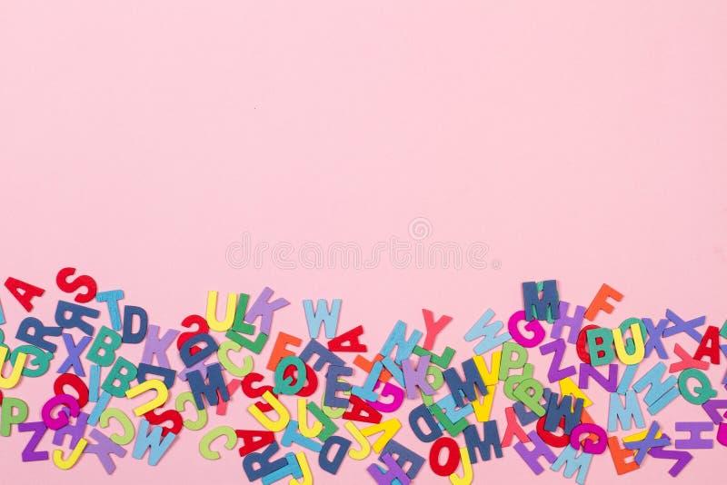 Kulöra bokstäver på en rosa bakgrund royaltyfria bilder