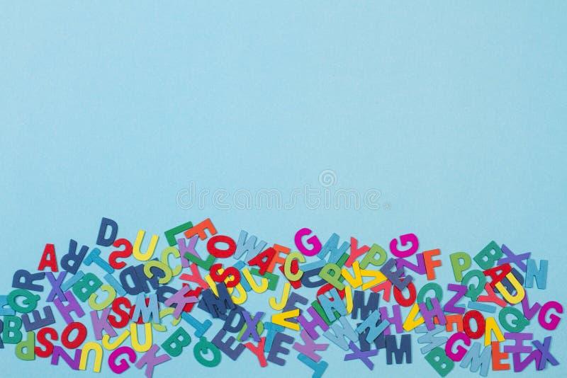 Kulöra bokstäver på ett ljust - blå bakgrund arkivbilder