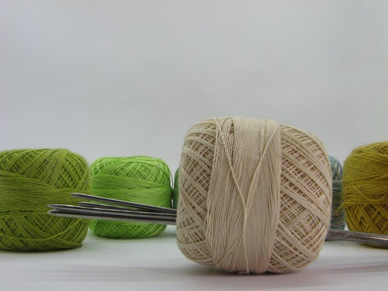 Kulöra bomullsbollar med att sticka trådar på en vit bakgrund royaltyfri bild