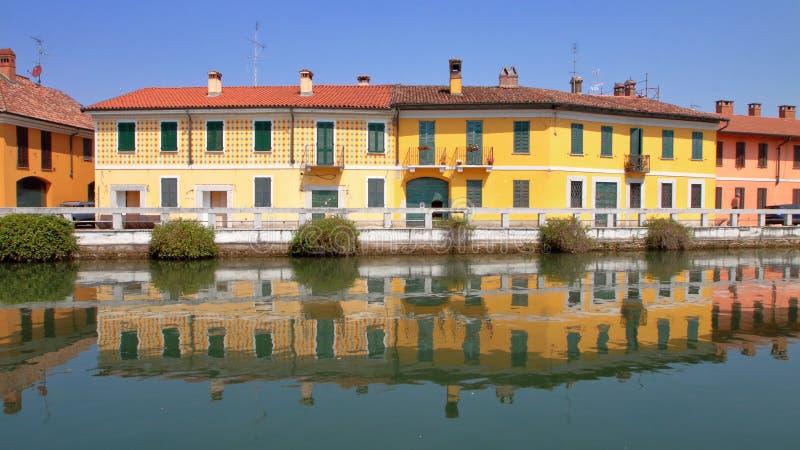 Kul?ra byggnader med reflexioner i vattnet i Italien royaltyfri foto