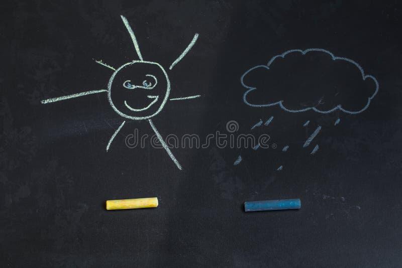 Kulöra chalks, svart svart tavla med teckningar av solen och ett moln arkivfoto