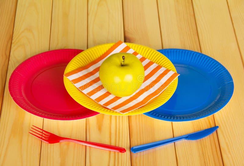 Kulöra disponibla plattor, plast- kniv, gaffel, äpple på ljust trä arkivfoto