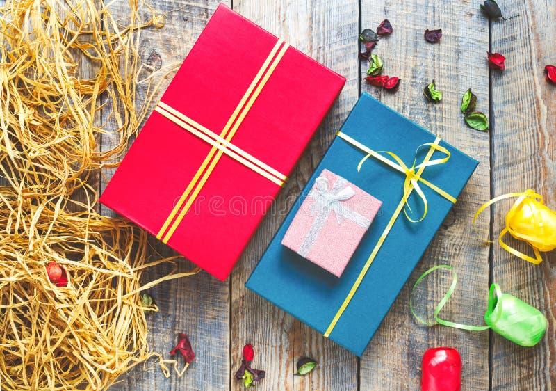 Kulöra gåvaaskar på träbakgrund med band arkivfoton