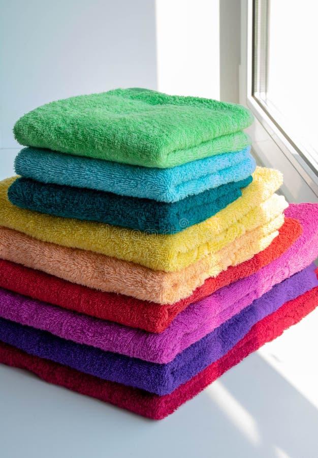 Kulöra handdukar på ett soligt fönster arkivbild