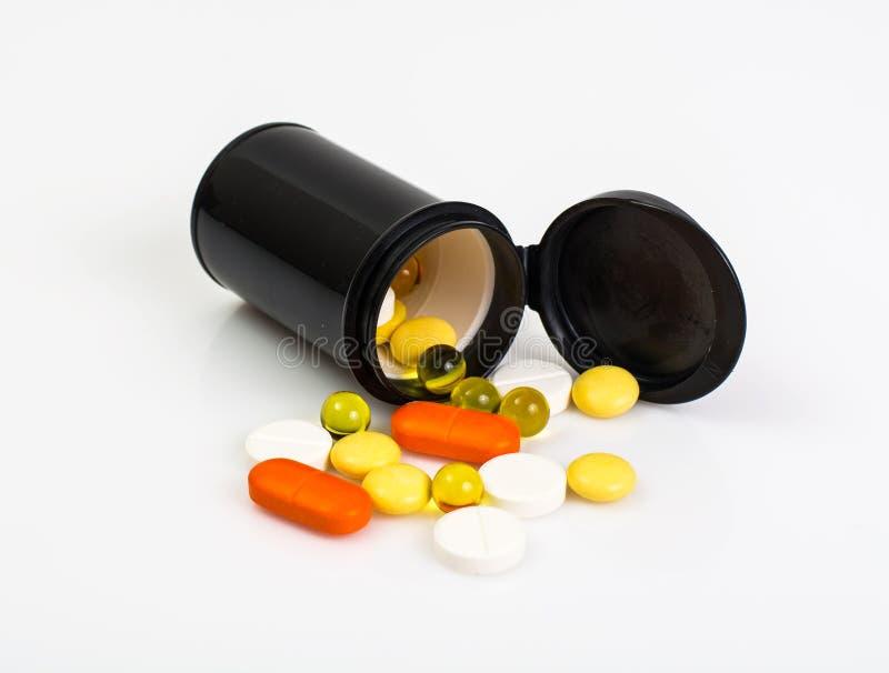 Kulöra kapslar, minnestavlor och preventivpillerar i en plast- krus arkivfoto