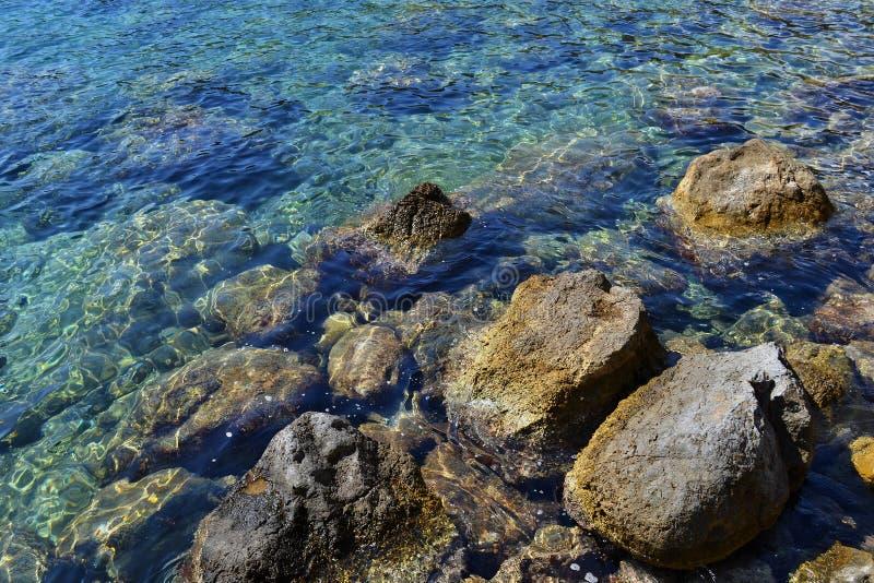 Kulöra kiselstenar under vatten på kusten av medelhavet royaltyfri bild