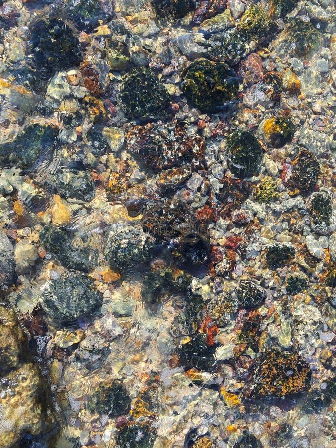 Kulöra kiselstenar under vatten på kusten av medelhavet royaltyfria foton
