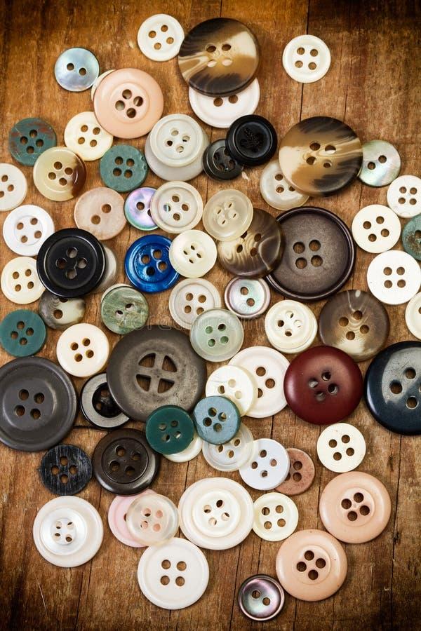 Kulöra knappar på en trätabell royaltyfri fotografi