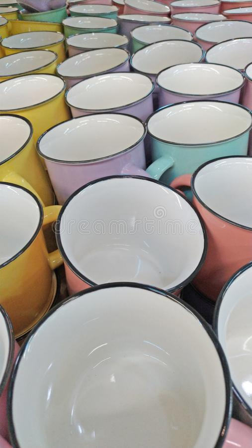 Kulöra koppar för järn i pastellfärgade färger eller signaler Tappningkoppar för te ovanlig bakgrund arkivbilder