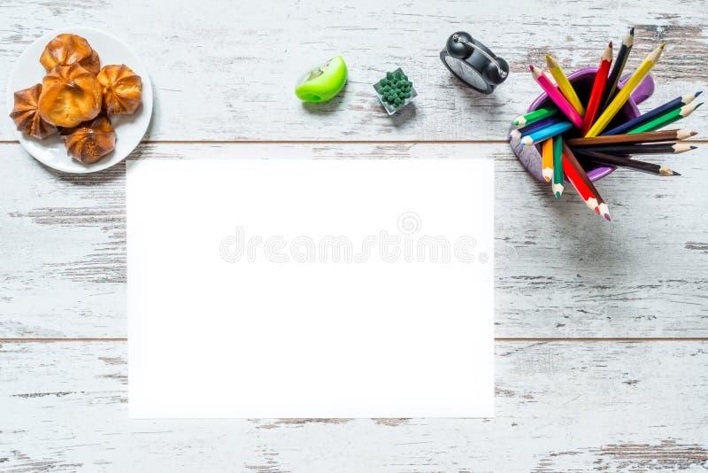 Kulöra mångfärgade blyertspennor, ett ark av vitbok, klocka för gammal stil, platta med kakan på tappningen träbakgrund arkivbild